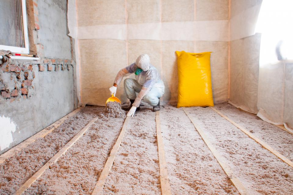 contractor installing cellulose insulation, wearing a protective suit